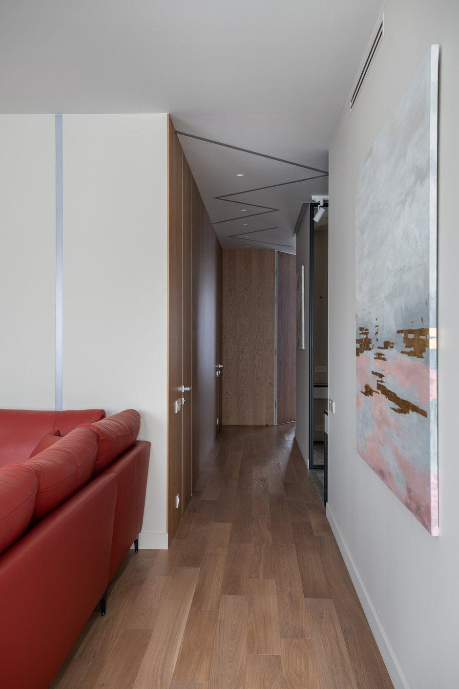 Стеновые панели с вертикальной текстурой дерева подчеркивают высоту потолка и позволяют удачно обыграть длинный коридор.